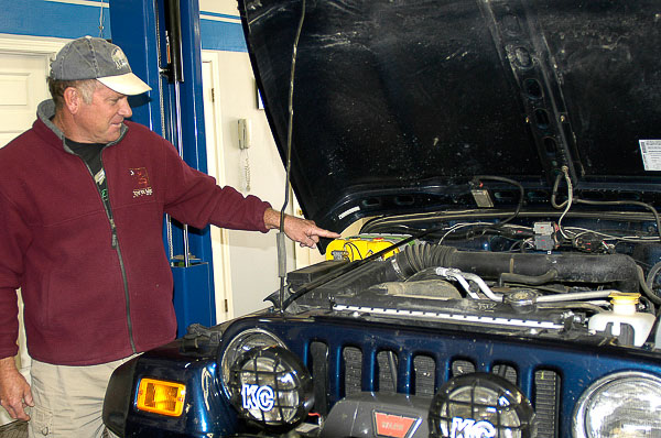 Student assesses his Jeep's battery.